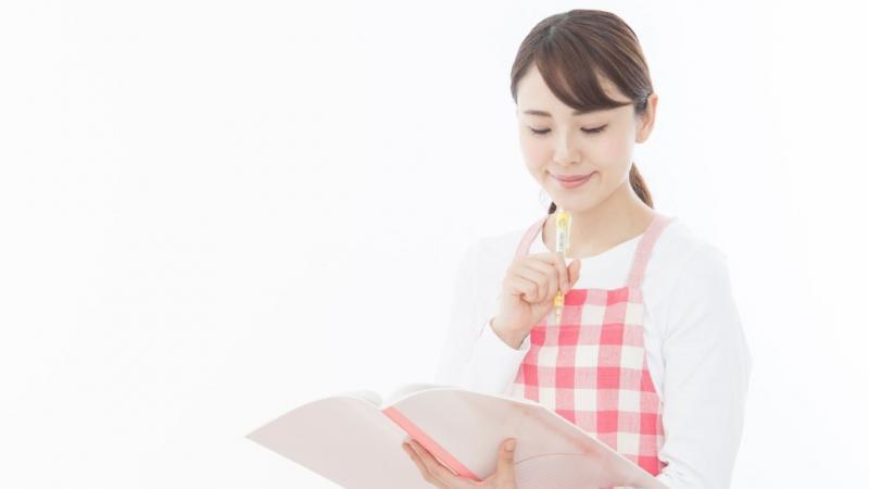 ノートを見て考えている女性