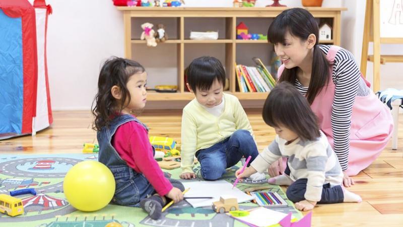 保育士と子どもがお絵描きをしているところ