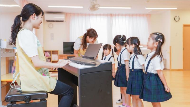 ピアノを弾く保育士と歌う子どもたち
