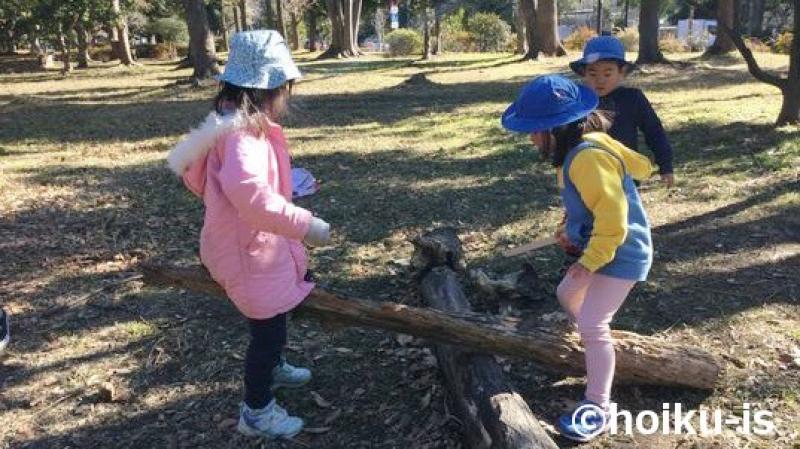 木の棒を見ている子どもたち