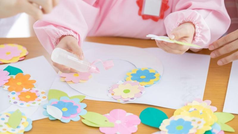 お花の飾りを作る子どもの手元