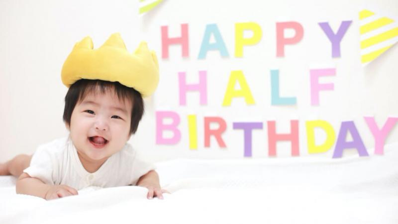 ハッピーバースデーの飾りと冠の帽子を被った赤ちゃん
