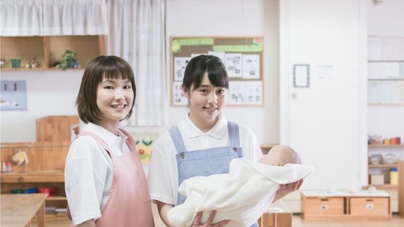 乳児を抱っこする保育士と見守る保育士