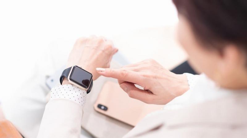 腕時計を操作する女性の手