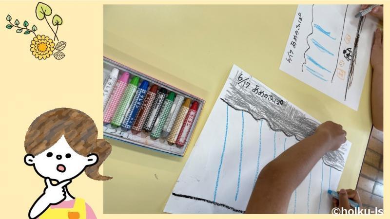 雨の日の絵を描いている子どもの手