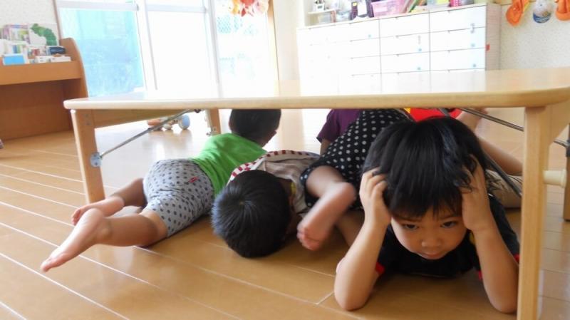 机の下に避難する子どもたち