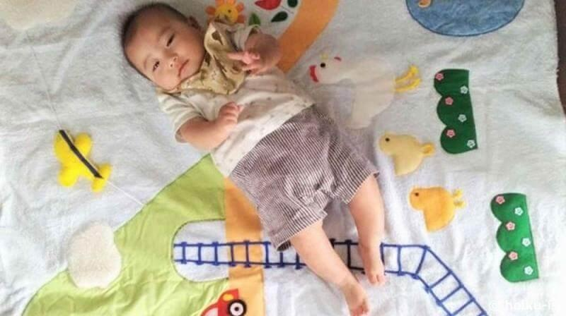 布おもちゃのマットに寝そべる赤ちゃん