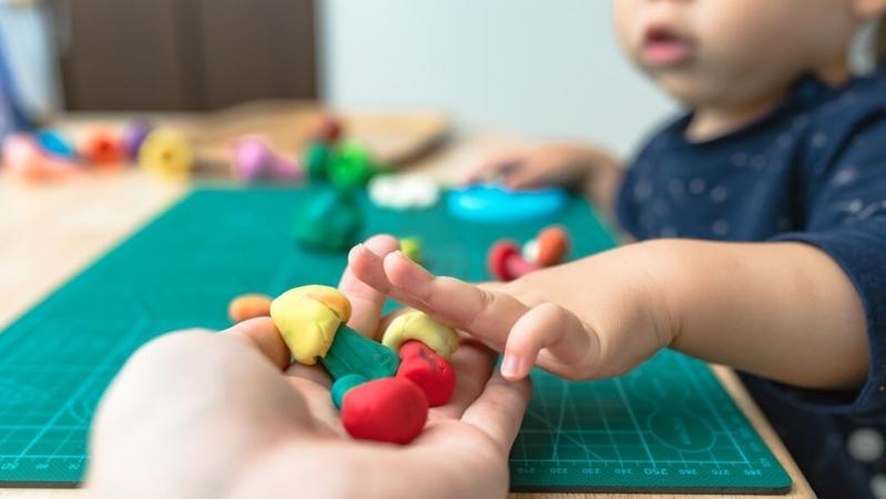 粘土に手を伸ばす子どもの手