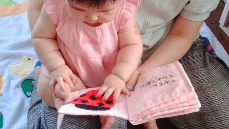 布おもちゃの布絵本で遊ぶ女の子