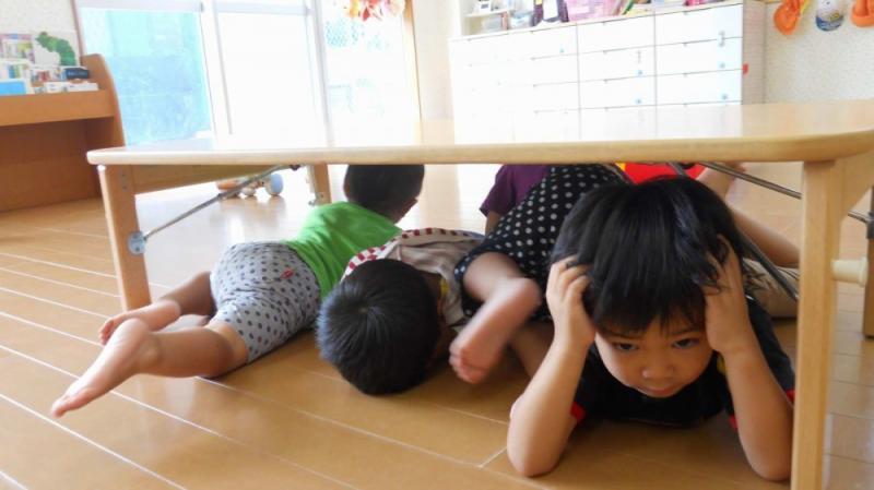 防災訓練で机の下に隠れる子どもたち