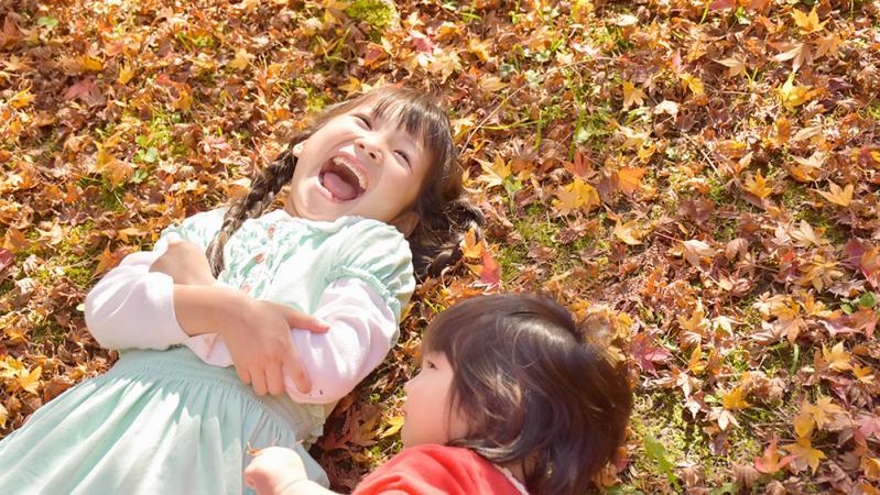 落ち葉に寝転ぶ子どもたち