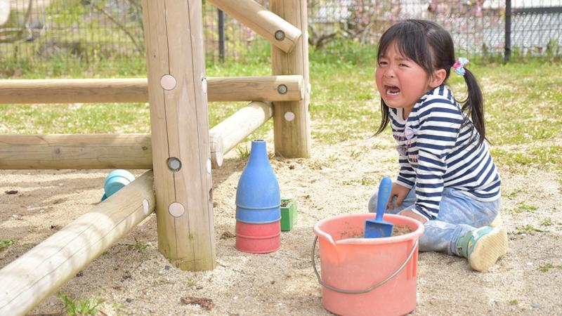 砂場で泣いている女の子