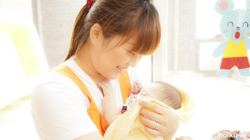 乳児を抱いている保育士