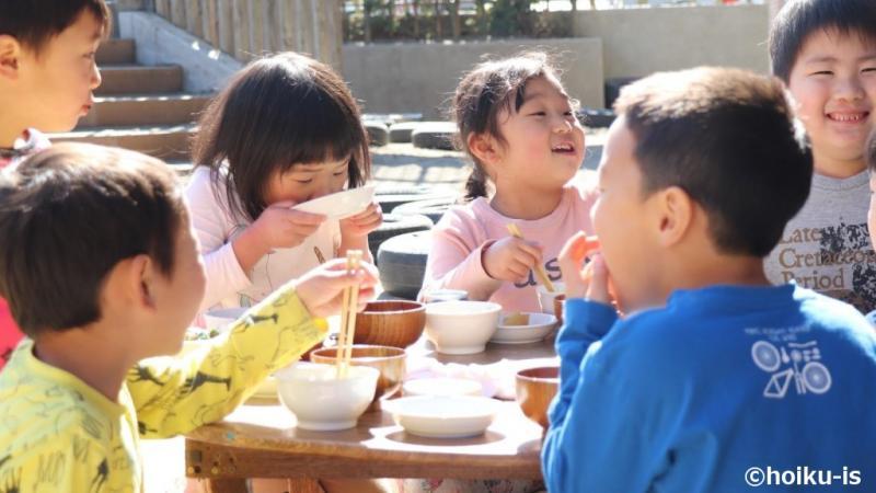 外で食事をする保育園の子どもたち