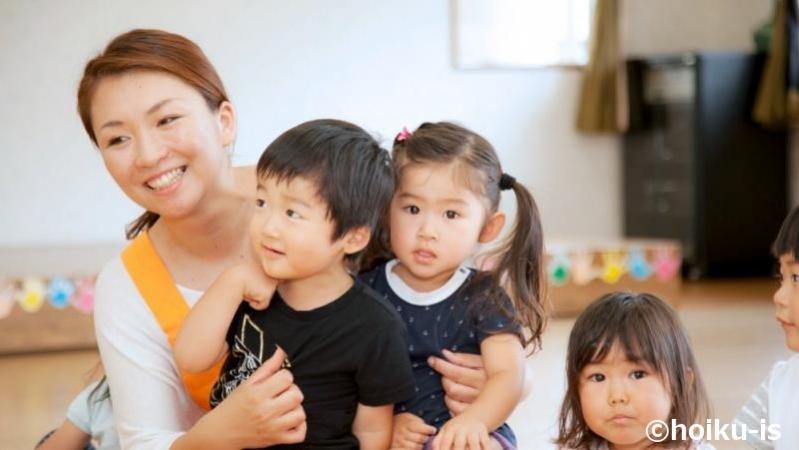 子どもを抱えている保育士
