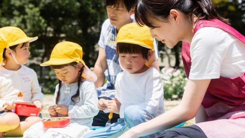 お弁当を食べる子どもたちと保育士