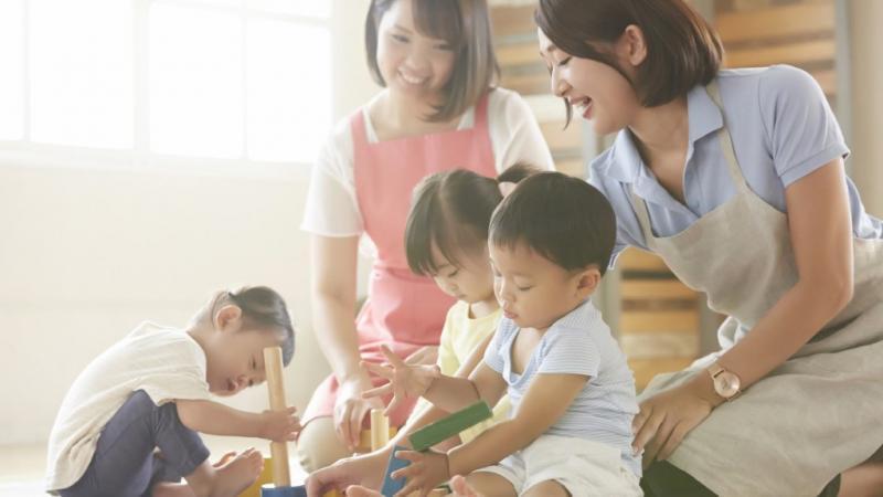 積み木で遊ぶ子ども達と保育士