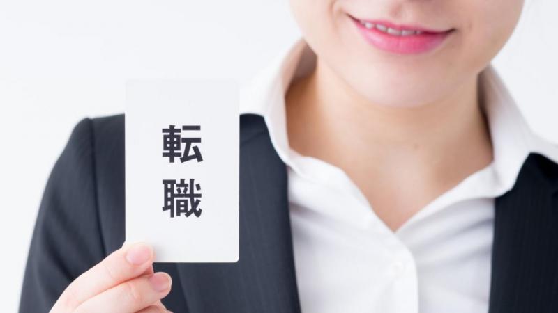 転職と書かれたカードを持つ女性