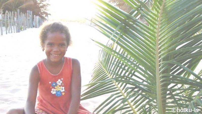 笑顔で砂浜に座るアンジェリーナ