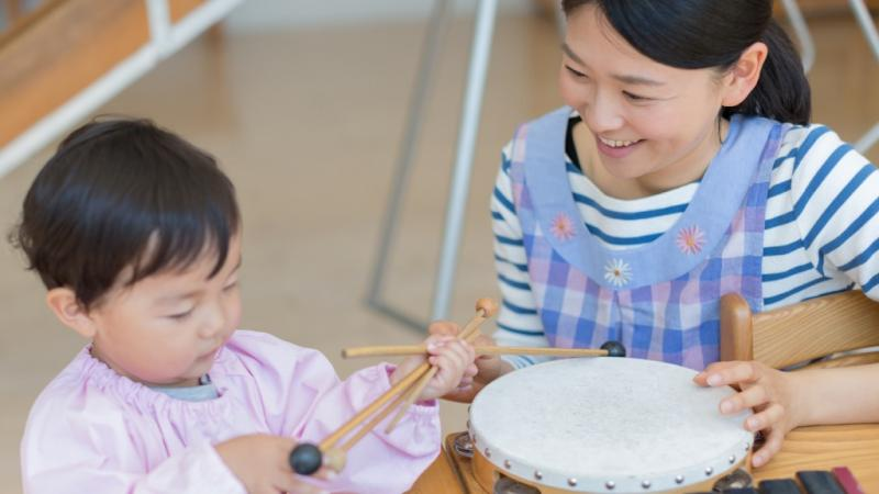 楽器に触れあう子どもと保育士