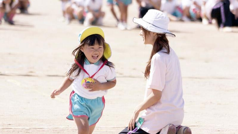 運動会で走っている子どもと見守る保育士