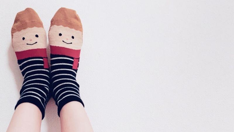 顔の柄が描かれている靴下を履いている足